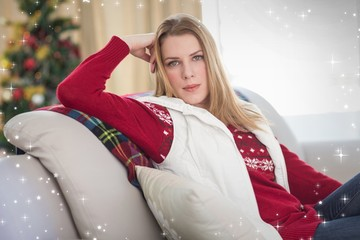 Composite image of cute blonde sitting on couch posing