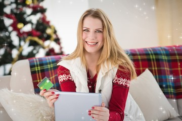 Cute blonde sitting on couch holding credit card and tablet