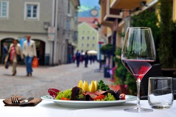 Composition with red wine and food in open restaurant