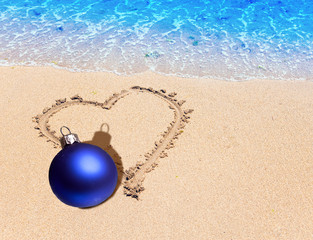 On sand heart is drawn and the New Year's blue ball lies