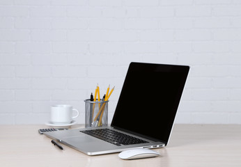 Modern laptop on table, on white wall background