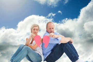 Composite image of sad mature couple holding a broken heart
