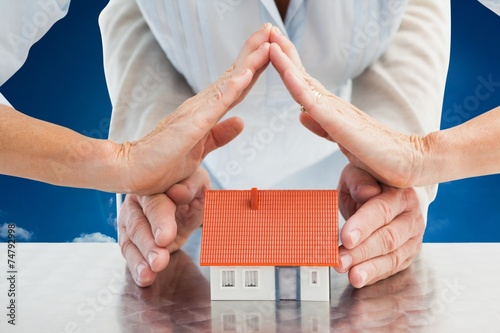 canvas print picture Composite image of couples hands with model house