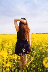 Girl with hand in hair on rapeseed meadow