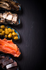 Fish assortment and olives on a plate on a dark background. With