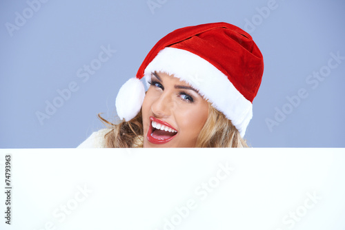 canvas print picture Laughing woman in a Santa hat with sign
