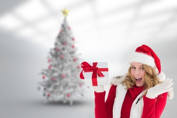 Composite image of excited blonde in santa hat holding gift