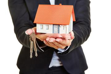 Hände vom Makler halten Haus und Schlüssel