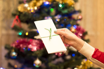 White gift envelope in a female hand with Christmas tree with or