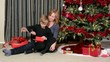 A boy opening a Christmas present with his mother