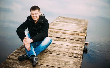 Young handsome man sitting on wooden pier, relaxing,  thinking.