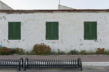 Casa con finestre verdi chiuse