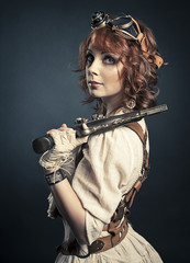 Beautiful redhair steampunk girl with gun looking at camera