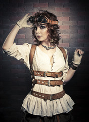 Beautiful redhair woman with steampunk goggles