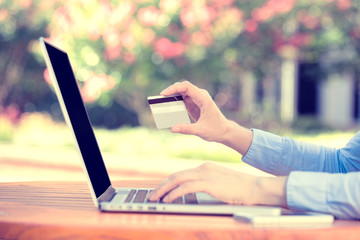 woman hands holding credit card and using computer