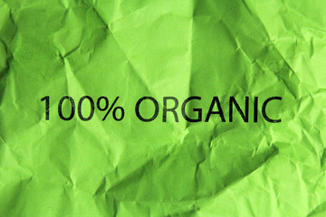 100% organic text on crumpled green paper