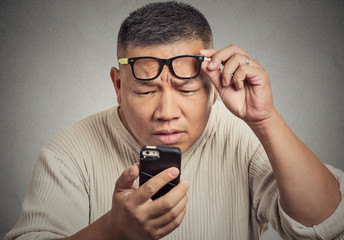 man with glasses having trouble seeing phone screen