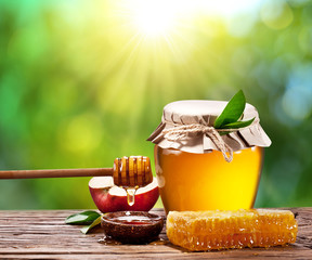 Glass can full of honey, apple and combs.