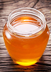 Glass can full of honey on wooden table.