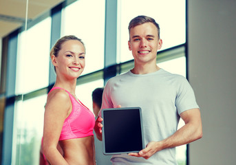smiling young woman with personal trainer in gym