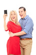 Excited couple taking a selfie with mobile phone
