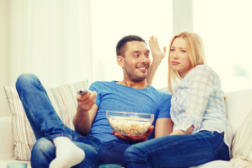 smiling couple with popcorn choosing what to watch