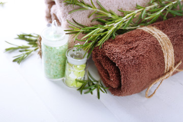 Branches of rosemary, towels and bottle with sea salt