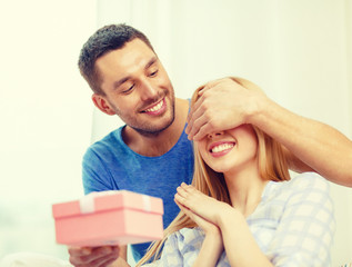 smiling man surprises his girlfriend with present