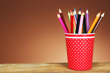 Colorful pencils in red plastic cup