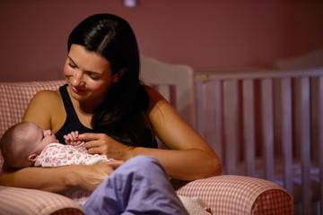 Mother At Home Cuddling Newborn Baby In Nursery