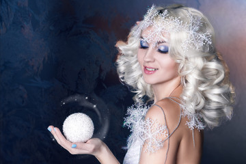 Snow Queen with frozen makeup holding a snowball