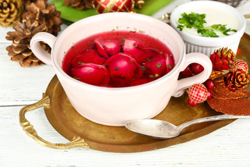 Traditional polish clear red borscht with dumplings in bowl