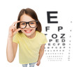 smiling little girl in eyeglasses with eye chart