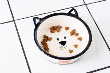 Few heart shaped dry cat food in cat shaped dish