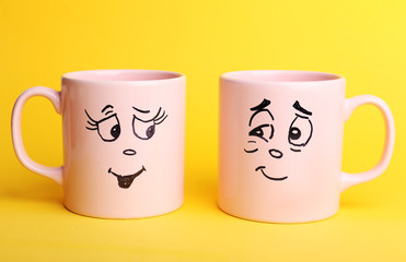 Emotional cups on yellow background