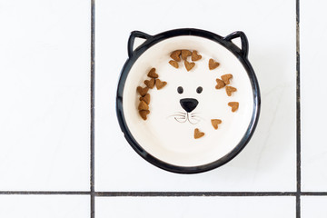 Some heart shaped dry cat food in cat shaped dish
