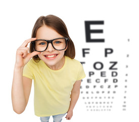 smiling little girl in eyeglasses with eye chart