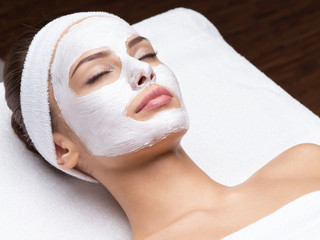 woman relaxing in spa salon with cosmetic mask on face