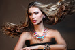 Fashion model with long curly hair posing in exclusive jewelry