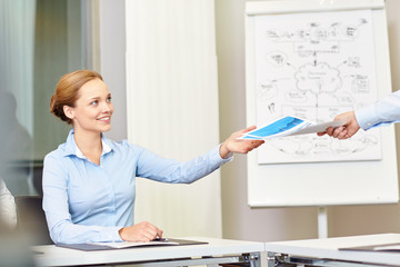 businesswoman taking papers from someone in office