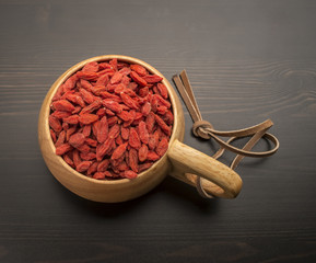 Goji berries in a wooden bowl, which stands on a black table
