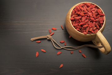 Goji berries in a wooden bowl on the table