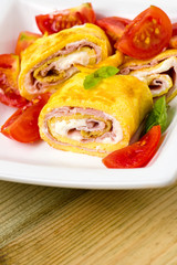 delicious rolls omelette with tomato, ham and cheese cream