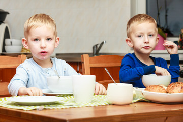 Kids children eating flakes breakfast meal at the table