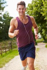 Man Running In Countryside Wearing Earphones