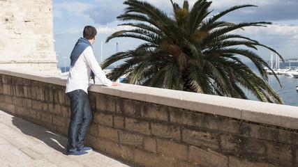 Ragazzo cammina per strada vicino al mare