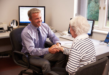 Doctor Greeting Senior Female Patient With Handshake