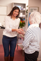 Receptionist Greeting Female Patient At Hearing Clinic