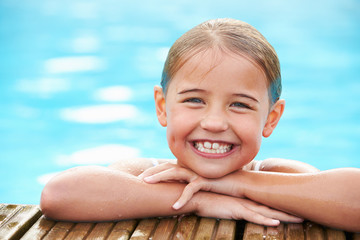 Young Girl Resting On The Edge Of Swimming Pool