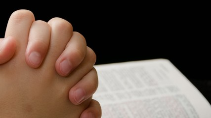 Clasped hands of child praying over Bible